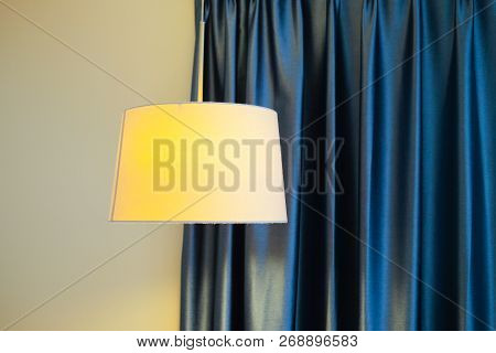 Modern Lamp With Blue Curtain. Warm Orange Light