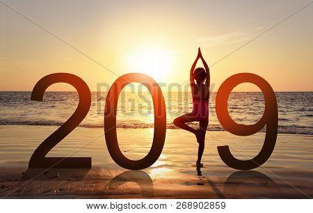 Happy New Year Card 2019. Silhouette Of Healthy Girl Doing Yoga Vrikshasana Tree Pose On Tropical Be