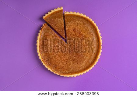 Minimalist Image Of A Pumpkin Pie, With One Sliced Piece And Separated, On A Purple Background. Top