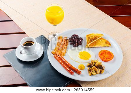Early Tasty Breakfast With Coffee And Juice. Eggs Sausages And Bacon