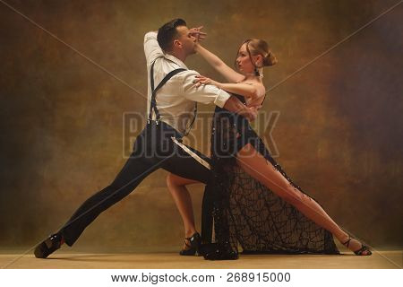 Flexible Young Modern Couple Dancing Tango In Studio. Fashion Portrait Of Attractive Dancing Couple.