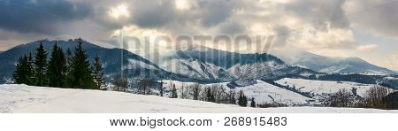 Panorama Of A Mountainous Countryside In Winter. Small Forest On The Hill And Village Down In The Va