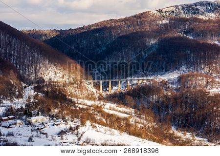 Winter Rail Road Transportation In Mountains. Station And Village On Hill And Viaduct In The Distanc