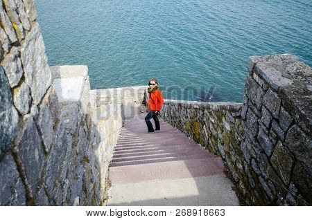 Adult Female Walks Down On The Forty Steps On The Rhode Island Cliff Walk On A Spring Day