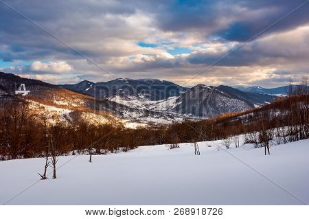 Beautiful Winter Landscape Of Carpathians. Village Down In The Valley In Dappled Light. Gorgeous Eve