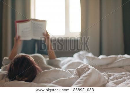 Teen girl in sweater reading a book in a hotel bedroom in the morning