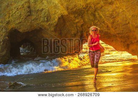 Happy Blonde Woman Running On The Seashore Of Popular El Matador Beach. Sporty Girl Jogging On The S