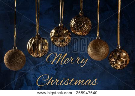 The inscription Merry Christmas on a dark blue background with textures and decorative putty. Six golden christmas balls hanging on ribbons. poster