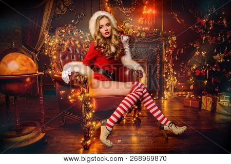 Sexy Santa girl in red body suit and striped stockings poses in luxurious apartments decorated Christmas lights. Christmas and New Year concept.
