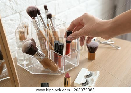 Woman Taking Cosmetics From Organizer For Makeup Products On Table