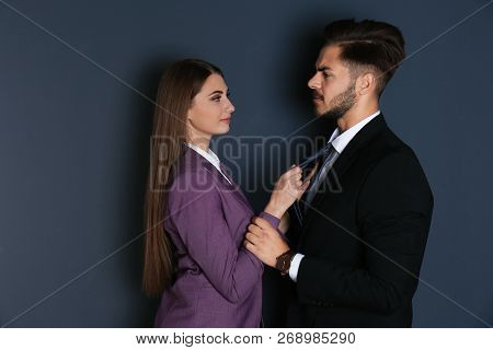 Woman Molesting Her Male Colleague On Dark Background. Sexual Harassment At Work