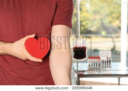 Man Holding Heart Near Hand With Adhesive Plasters At Hospital, Closeup. Blood Donation Concept