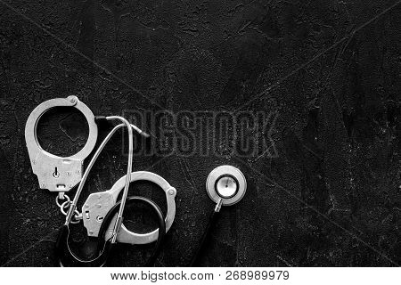 Medical Lawsuit. Arrest For Medical Crime Concept. Handcuff Near Stethoscope On Black Background Top