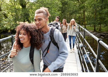 A mixed race couple and young adult friends crossing a wooden bridge over a river during a hike
