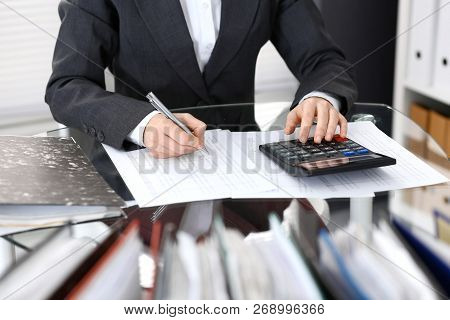 Bookkeeper woman or financial inspector  making report, calculating or checking balance, close-up. Business portrait. Copy space area for audit or tax concepts poster