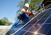 Technician installing solar photo voltaic panel to metal platform using screwdriver on bright blue sky copy space background. Stand-alone solar panel system installation concept. poster
