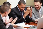 Multi ethnic business team at a meeting. Interacting. Focus on african-american man poster