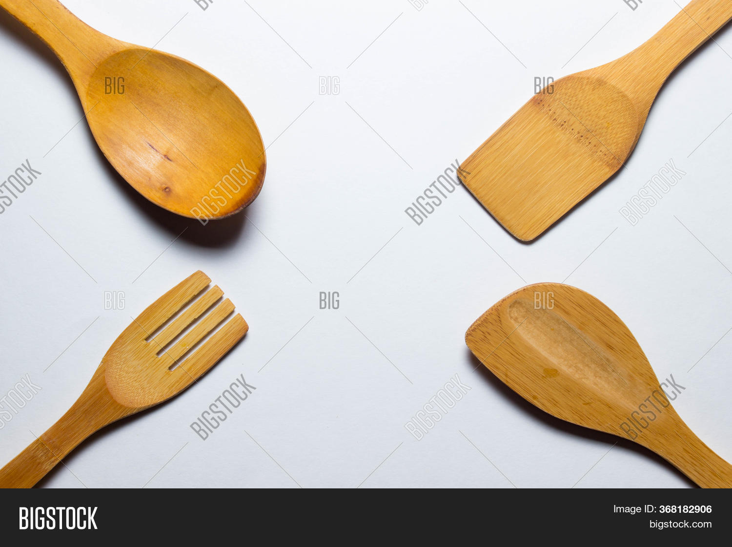 Four Wooden Cutlery Lie In Four Different Edges Of Photography On A White Background. Wooden Spoon,