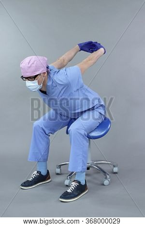 Caucasian dentist in uniform and mask and eyeglasses , stretching arms in studio - healthy lifestyle at work