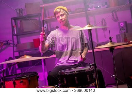 Guy in t-shirt, jeans and beanie sitting in garage in front of drum kit and going to hit cymbal and drum with drumsticks during rehearsal