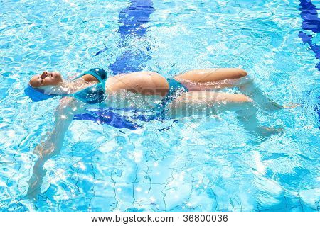 Beautiful Relaxed Pregnant Woman In Swimmingpool In Summer
