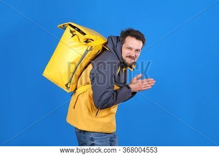 Sly Food Delivery Man With Yellow Thermos Bag Is Making Face And Rubbing His Hands In Anticipation O