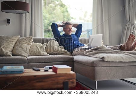 man with laptop on a sofa at home