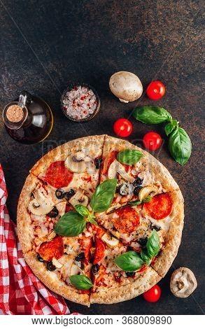 Sliced Italian Pizza With Salami, Mozzarella, Mushroom, Tomatoes, Black Olives And Basil Leaves On B
