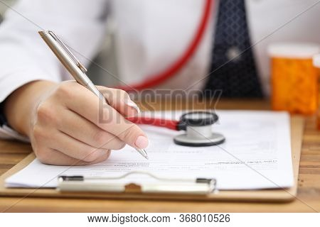 Doctor Makes Notes About Health In Patient Card. Medical Care, Health Status And Patient Diagnosis.