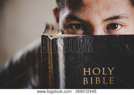 Close-up Of Young Man Student Reads A Holy Bible