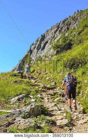 Hikers With Hiking Poles In French Alps Near Chamonix On A Trail To Lac Blanc With Mont Blanc View.