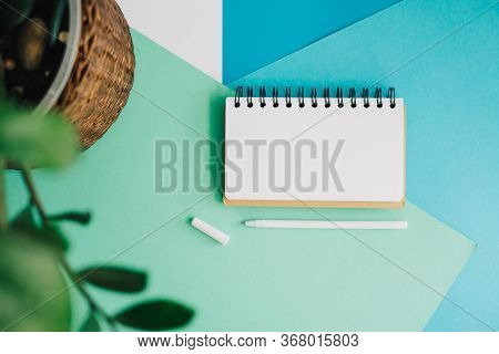 A Notebook On An Abstract Background. White Notepad Page And Pen For Writing. Abstract Background Of