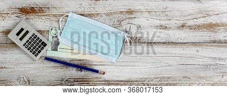 Economic Impact Stimulus Check On White Wooden Working Desktop With Personal Protection Mask