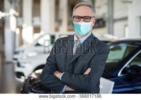 Masked car dealer principal inside showroom during coronavirus pandemic