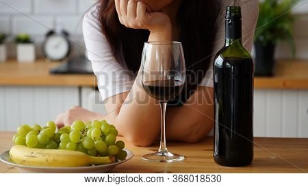 Young Woman Drinking Red Wine At Table. Close Up Of Adult Female Takes Glass Of Wine, Sitting In Kit