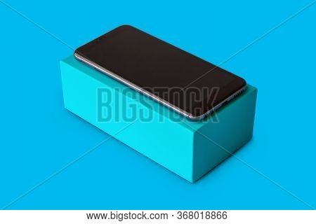 Blue Cardboard Box With A Smartphone On Blue Background For Mockup,  Rectangular Box Mockup For Smar
