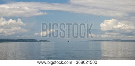 Sailboat Between Bainbridge Island And Shoreline With Cumulus Clouds Casting Shadows On Water, Shore