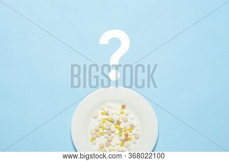 A Lot Of Pills On A White Plate And A Question Mark On A Blue Background. Insomnia, A Choice Of Drug