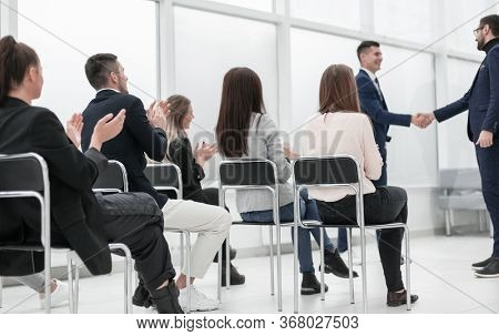 group of young people sitting on chairs in the conference room