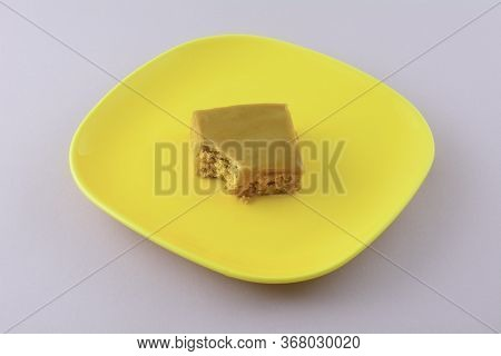 Toffee Flapjack Square Cake Bar With Bite Missing On Yellow Plate On Lavender Background