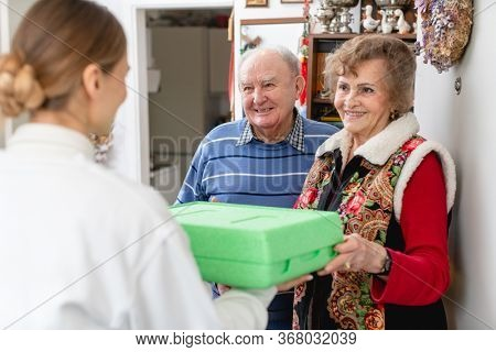 Senior couple greeting volunteer woman delivering a hot meal to their door