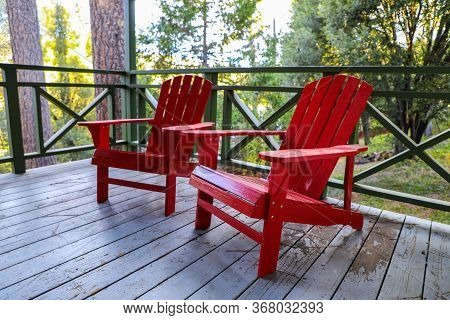 Red Adirondack Chairs Serenely Sitting Outside A Cabin In The Forest