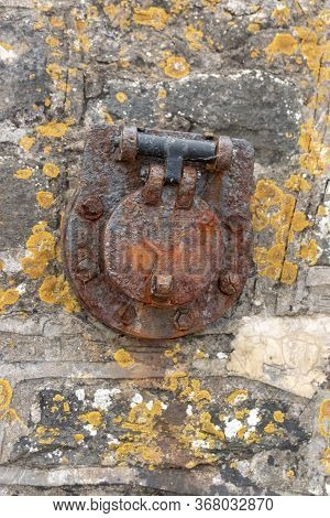 A Close Up View Of A Rusted Metal Port Hole That Is Attached To The Main Stone Wall Of A Old Docking