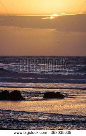 Sunset Scene In Gold Beach Oregon With Colorful Clouds And Waves Adding Reflected Color To Wet Sand
