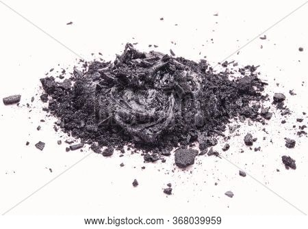 Liquid and solid black natural cosmetic activated charcoal or volcanic clay with scrub effect on white background.