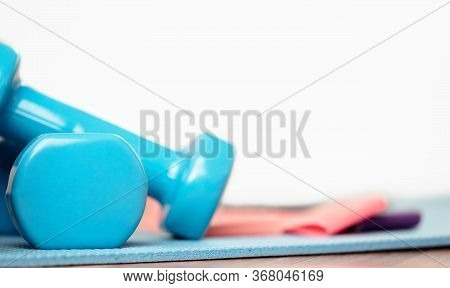 Blue Dumbbells For Power Exercises On Sports Mat. Strength Exercises. Healthy Lifestyle. Isolation P