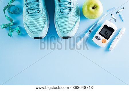Top View Of Diabetes Tester Set With Athlete's Equipment; Measuring Tape, Green Dumbbell And  Fruit