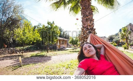 A Smiling Woman Is Lying In A Hammock. The Girl Is Resting In Nature. Camping. Holidays In Turkey. T