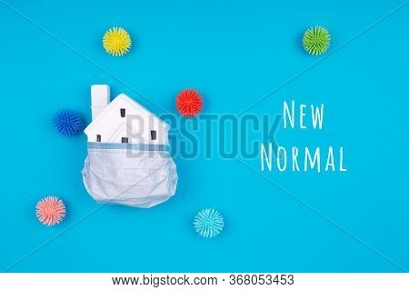 Cute Little House Covered With Medicine Mask And Plastic Balls As Viruses On Blue With New Normal Wo