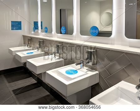 Distance Stickers And Signs Fixed Over The Sinks, Mirrors In A Public Toilet For The People To Follo